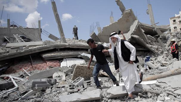 An elderly Palestinian man makes his way over the rubble of a destroyed house following Israeli strikes in Rafah (AP)