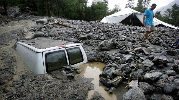 An official from the Forest Home Christian Conference Centre in Forest Falls, California, inspects damage on the property following thunderstorms (AP/The Press-Enterprise, David Bauman)