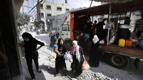 Members of the Palestinian Shabat family return to the family home, destroyed by Israeli strikes in the town of Beit Hanoun, northern Gaza Strip (AP)
