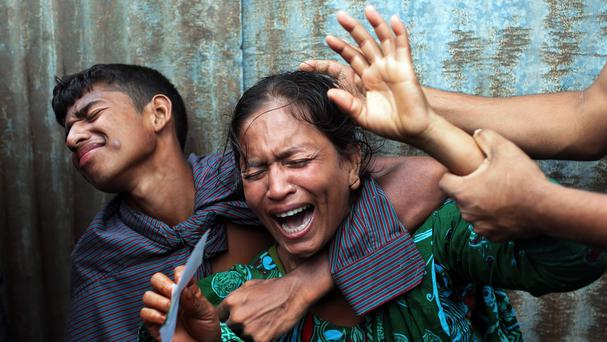 A Bangladeshi woman whose daughters are missing cries as rescuers search the River Padma after a passenger ferry capsized (AP)