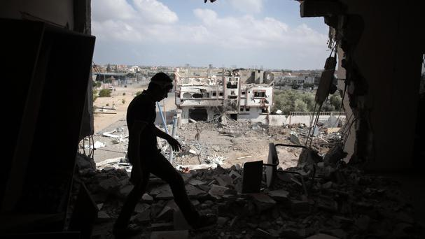 A Palestinian walks through a destroyed house in the southern Gaza Strip (AP)
