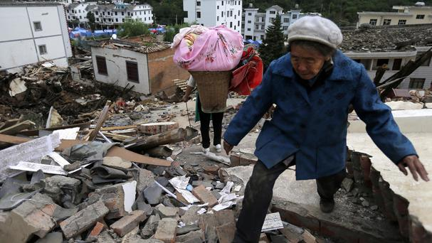 Villagers walk through rubble from destroyed houses following a massive earthquake in China (AP)