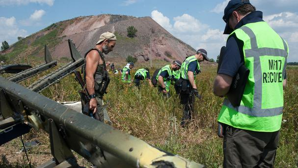 A pro-Russian rebel (left) guards as Australian, Malaysian and Dutch investigators examine the area of the downed Malaysia Airlines Flight 17 (AP)