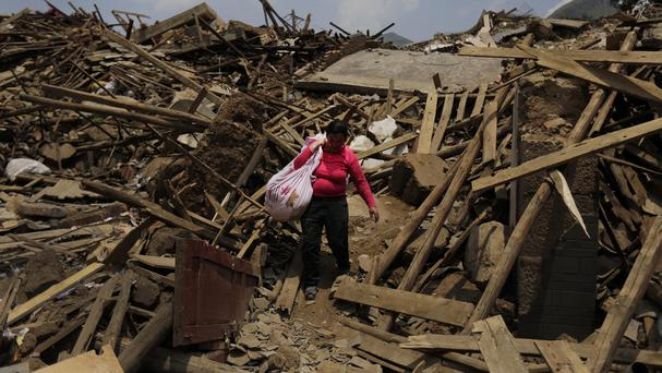 A woman carries her salvaged goods through the rubble of destroyed houses in the town of Longtoushan in China's Yunnan Province (AP)