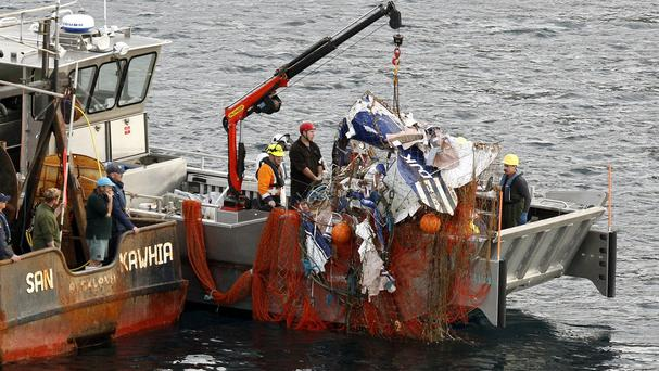 The wreckage of a plane is hauled on to a fishing boat off the southern point of Great Barrier Island near Auckland, New Zealand (AP)
