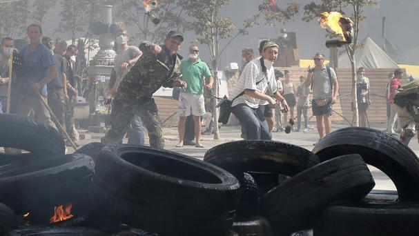 Activists throw a fire bomb during clashes with special forces police in Independence Square, Kiev (AP)