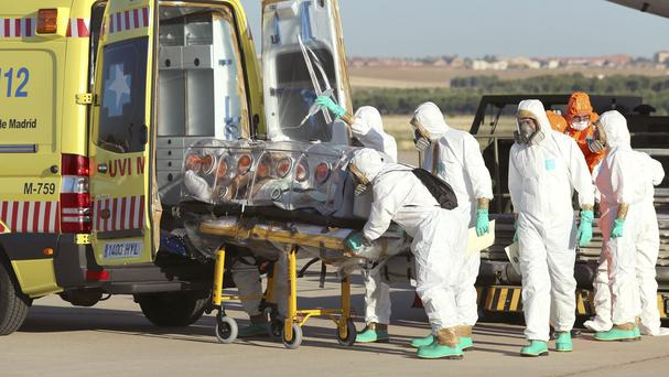 Aid workers and doctors transfer Miguel Pajares, a Spanish priest infected with Ebola in Liberia, from a plane to an ambulance (AP/Spanish Defence Ministry)