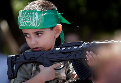 A Palestinian by holds a toy gun as he participates at a Hamas rally in Gaza City, Gaza Strip, Thursday, Aug. 7, 2014.