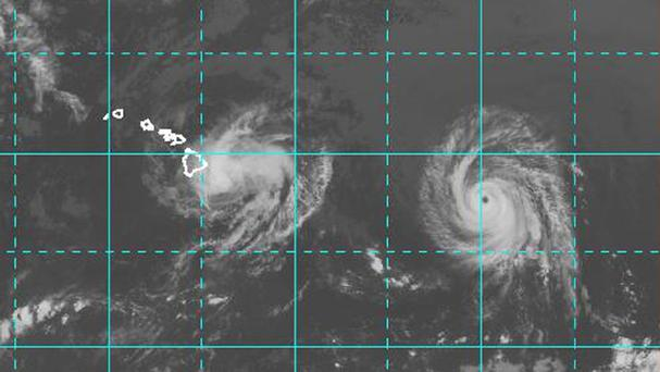 This satellite image shows Iselle approaching the Island of Hawaii, left, as Hurricane Julio with a well defined eye follows. (AP)