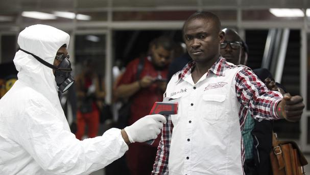 A Nigerian health official uses a thermometer on a worker at Murtala Muhammed International Airport in Lagos (AP)