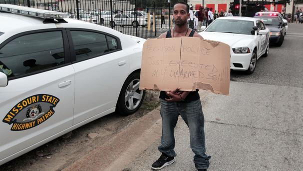 Louis Head, stepfather of 18-year-old Michael Brown who was fatally shot by police, holds a sign in Ferguson (AP)