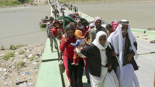 Displaced Iraqis from the Yazidi community cross the Syria-Iraq border at Feeshkhabour bridge over the Tigris River (AP)