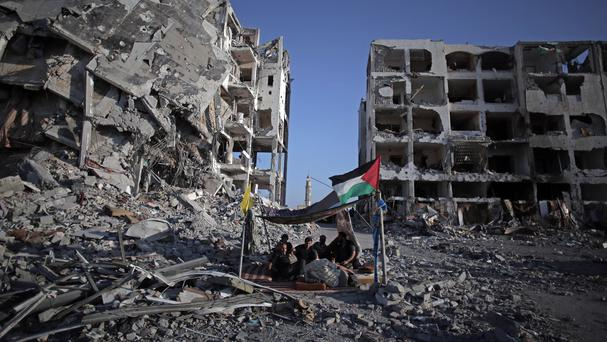 Palestinian Ziad Rizk, 38, sits with others in a shelter next to one of the destroyed Nada Towers, where he lost his apartment and clothes shop (AP)