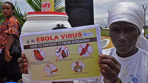 A Liberian woman holds up a pamphlet with guidance on how to prevent the Ebola virus from spreading, in the city of Monrovia (AP)