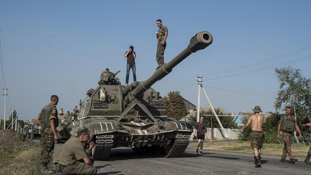 Ukrainian soldiers rest in their self-propelled guns as an army column of military vehicles prepares to roll to a front line in the Donetsk region (AP)