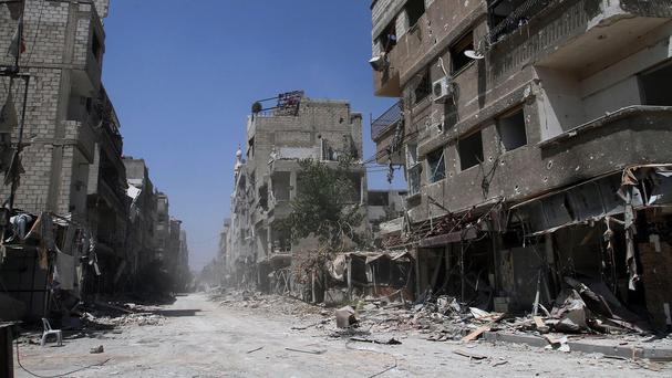 Buildings damaged during battles between Syrian troops and rebels in Mleiha (AP)