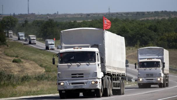 Trucks forming part of an aid convoy destined for Ukraine travel on a road to the border control point in the Russian town of Donetsk (AP)