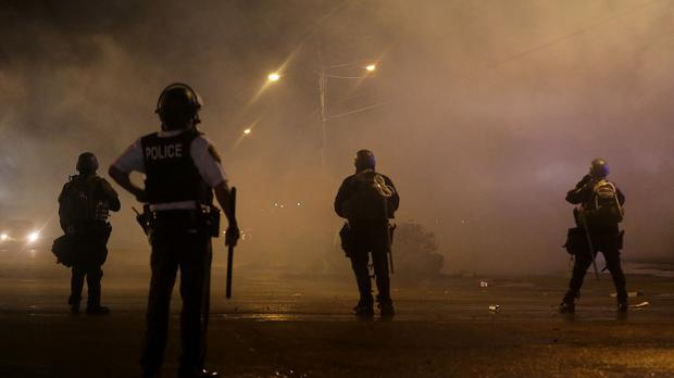 A law enforcement officer watches as tear gas is fired to disperse a crowd protesting the shooting of teenager Michael Brown last Saturday in Ferguson, Missouri (AP)
