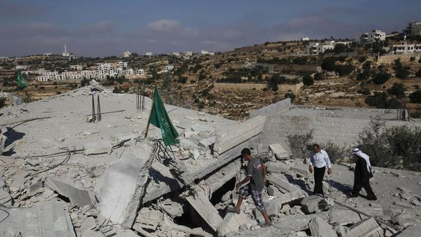 Palestinians walk on the rubble of the house of Hussam Qawasmeh after it was demolished by the Israeli army in the West Bank city of Hebron (AP)