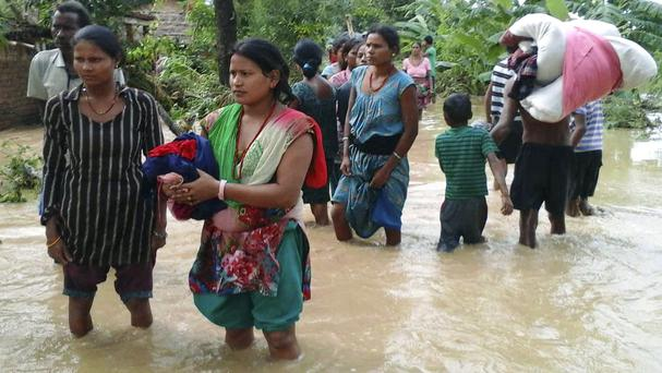 Nepalese villagers carry their belongings while wading through a flooded street to move to safer ground in Bardia (AP)