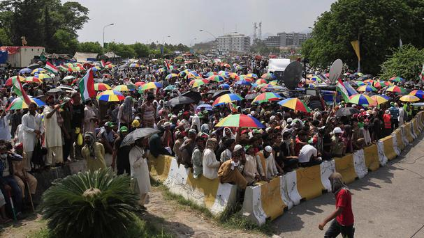 Supporters of anti-government cleric Tahir-ul-Qadri block an entrance of the parliament during a protest at Islamabad's high-security Red Zone (AP)