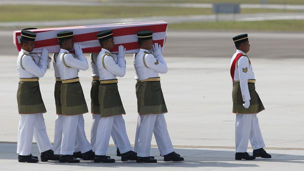 Malaysian Army soldiers carry a coffin containing one of the bodies of the downed MH17 flight (AP)