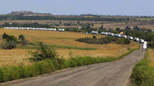 The first trucks of a Russian convoy roll on the main road to Luhansk (AP)