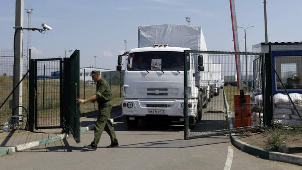 A Russian border guard opens a gate into the Ukraine for the first trucks heading into the country (AP)