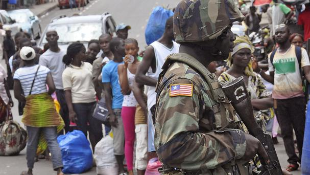 A Liberian soldier scans people for signs of the Ebola virus, as they control people from entering the West Point area in the city of Monrovia (AP)