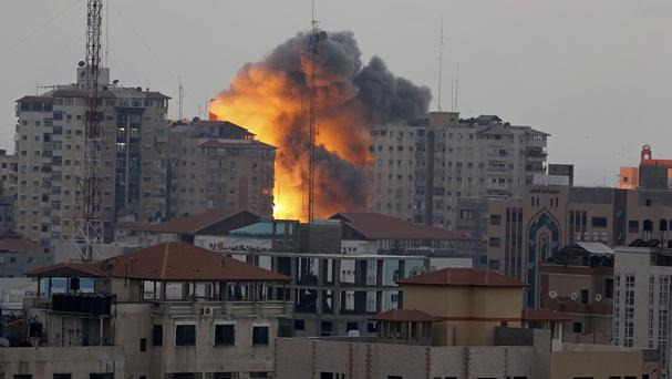 A ball of fire rises from an explosion at an apartment tower following an Israeli air strike in Gaza City (AP)