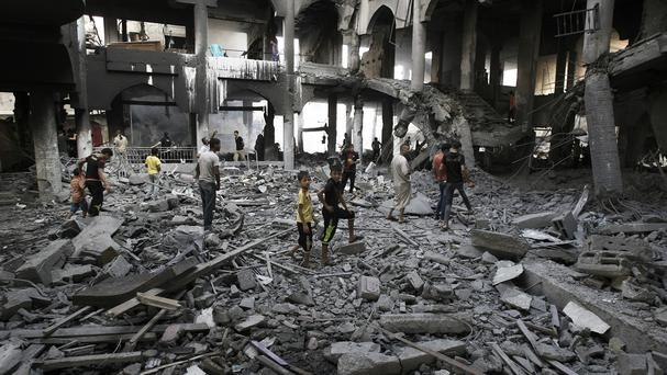 Palestinians inspect the damage to a Rafah commercial centre after an Israeli strike (AP)