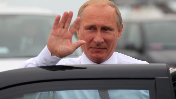 Russian president Vladimir Putin waves on his arrival in Minsk, Belarus (AP)