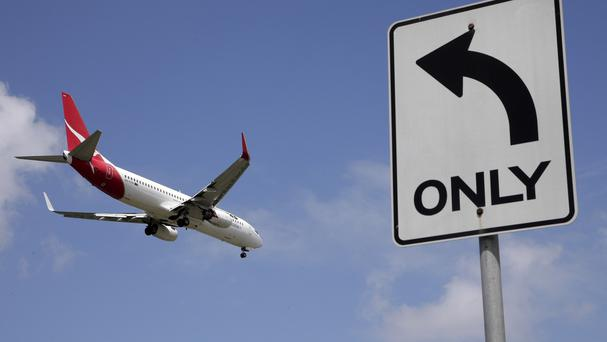 Australian flag carrier Qantas Airways has posted a record £1.5bn loss for the last fiscal year (AP)