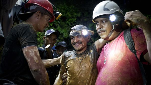 A rescued miner, centre, is greeted by a colleague while being helped by a rescue worker as he leaves the El Comal gold and silver mine (AP)