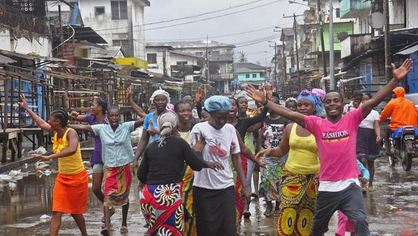 People celebrate on the streets outside a slum which had been closed off in a attempt to control the Ebola outbreak, in Monrovia, Liberia (AP)