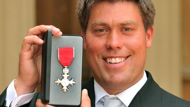 Olympic sailing gold medallist Andrew 'Bart' Simpson shows off his MBE in 2009