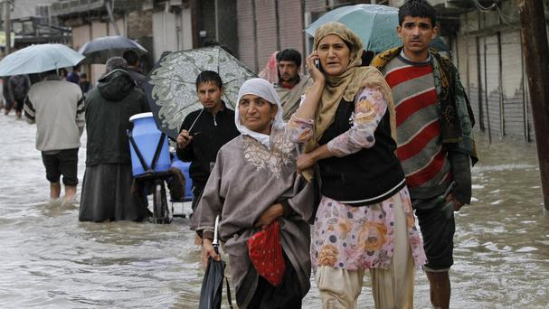 Kashmiris wade through floodwaters in Srinagar, India (AP)