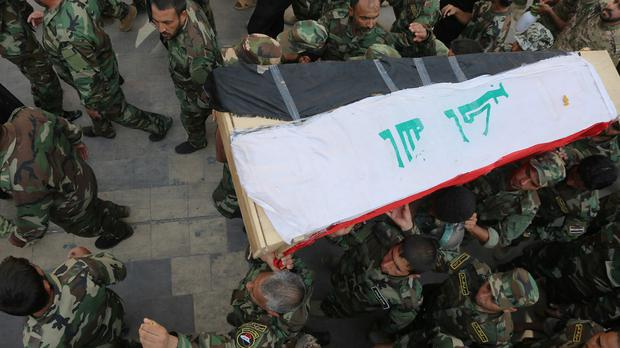 Shiite militiamen carry the flag-draped coffin of their colleague who was killed during clashes with Islamic militants in the town of Amirli, Iraq (AP)