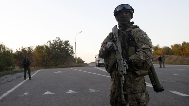 A Ukrainian soldier stands guard at a road during a prisoner exchange near the town of Donetsk, eastern Ukraine (AP)