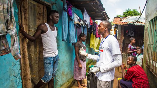A health worker volunteer talks with a resident on how to prevent and identify the Ebola virus in Freetown, Sierra Leone (AP)