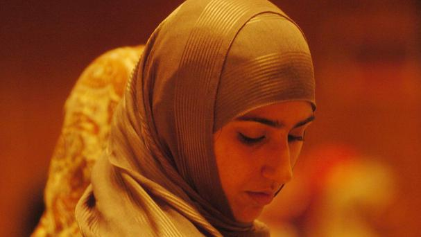 A Muslim woman wears a hijab, which is a scarf that covers the head and neck but does not obscure the face
