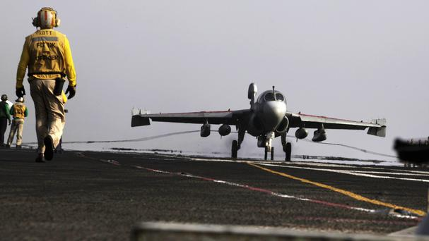 A US warplane lands on the USS George HW Bush aircraft carrier in the Persian Gulf (AP)