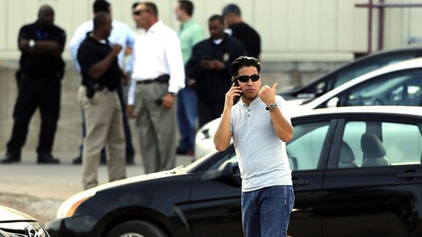 Employees wait in the car park as police investigate an incident at Vaughn Foodsin Moore, Oklahoma (AP)