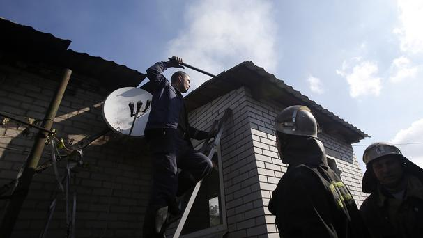 Firefighters try to extinguish a blaze at a damaged house after shelling in the town of Donetsk, eastern Ukraine (AP Photo/Darko Vojinovic)