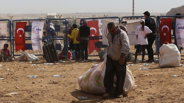 A Syrian refugee from Kobani carries his belongings as he arrives at the Turkey-Syria border near Suruc (AP)