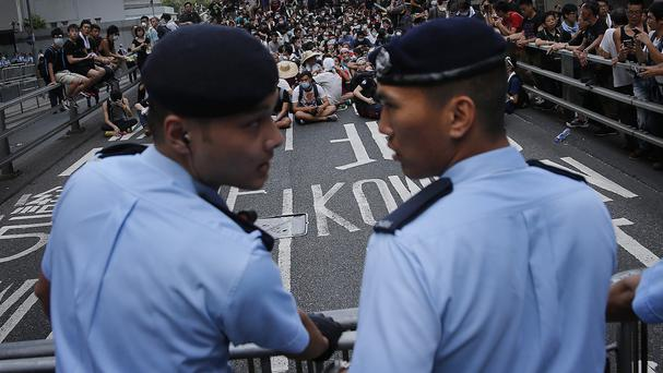 Pro-democracy protesters sit on a road as they face-off with local police in Hong Kong (AP)