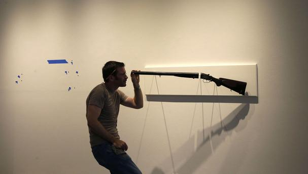 Artist Adam Mysock installs his artwork, titled Looking Down The Barrel of a Gun (The Last Judgement), at the Guns in the Hands of Artists exhibition (AP)