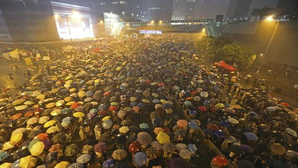 Pro-democracy protesters brave heavy rain in a main street near the government headquarters in Hong Kong. (AP)