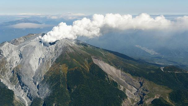 An aerial view shows volcanic fume and smoke raising from craters of Mount Ontake in central Japan (AP/Kyodo News)