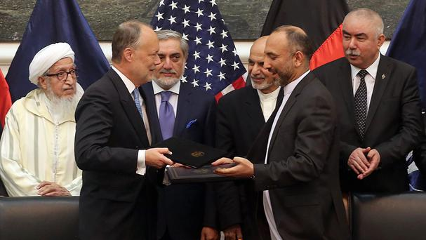 US ambassador James Cunningham and Afghan security chief Mohmmad Hanif Atmar exchange documents in Kabul. (AP)